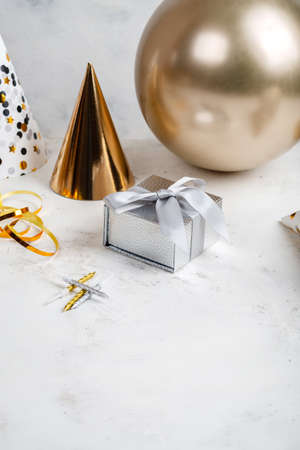 Festive composition Silver gifts box Golden party hat and balloon on white background with place for text Zdjęcie Seryjne