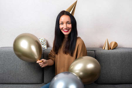 Smiling young woman wearing in party hat with balloons are celebrating birthday at home