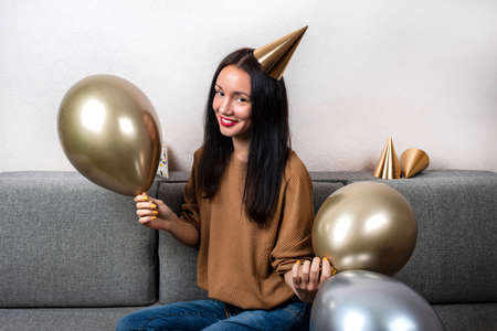 Young woman with golden silver balloons are sitting on the couch and celebrating birthday at home