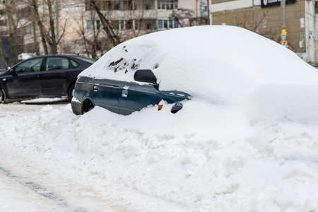 Car covered with snow in the street yard