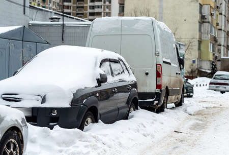 Cars stand in the yard covered with snow Stock fotó