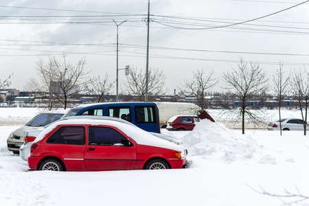 Frozen and snow covered automobiles cars in the city yard