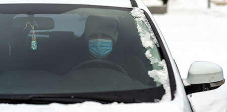 A man sits in a car wearing a virus-protective mask close-up Zdjęcie Seryjne