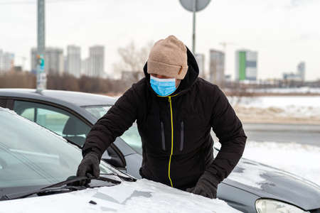 Man in a protective mask cleaning car windshield from snow.