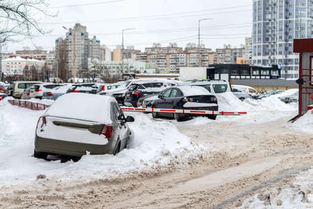 Cars covered with snow are parked along the building in thick fog and heavy snow Zdjęcie Seryjne