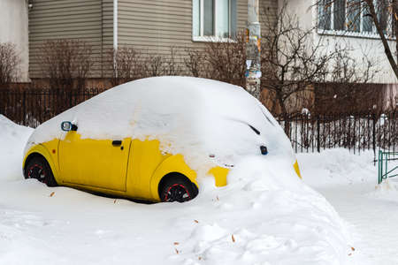 Car covered with snow in urban area