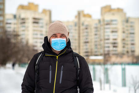 a man walking down the street wearing a protective mask middle plan Zdjęcie Seryjne