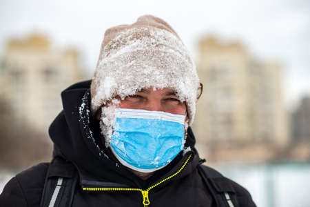 a man walking down the street wearing a protective mask close-up
