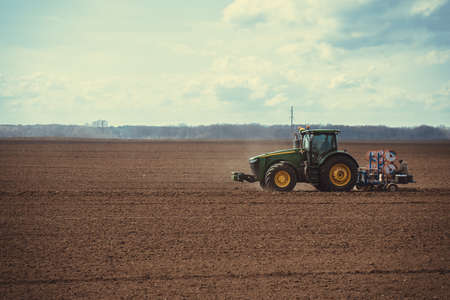 The tractor is laying the cable on the field Zdjęcie Seryjne