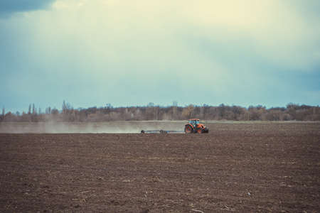 Farm tractor plows the field and prepares for sowing