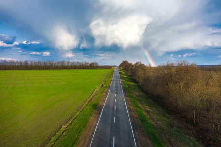 Rainbow over rural highway road spring landscape aerial view