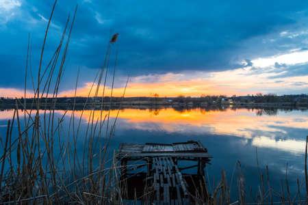 Old fishing wooden bridge on the lake at sunset Zdjęcie Seryjne