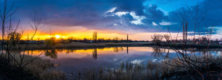 Beautiful golden sunset with reflection of clouds in the lake in the village panorama