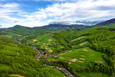 Snow-capped mountain peaks and beautiful forest mountains in summer aerial view. Zdjęcie Seryjne