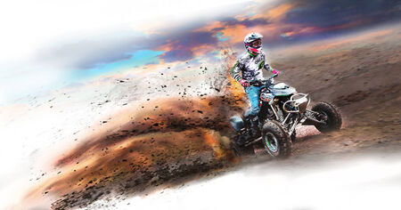 REAL QUAD BIKE FUN FOR BOYS A Photograph of a young man riding his quad bike or four wheeler with all the dirt and dust with flames behind the motor bike Editorial