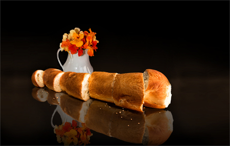glass plate: French Bread with flowers Cut in slices  on a glass plate with flowers in a vase, reflecting image , with black background Stock Photo