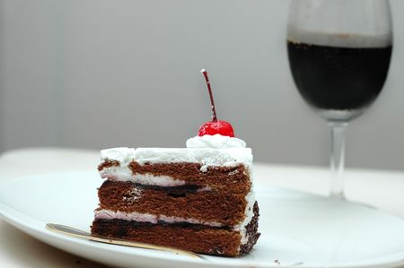 Piece of chocolate and cream cake with cherry on the top photo