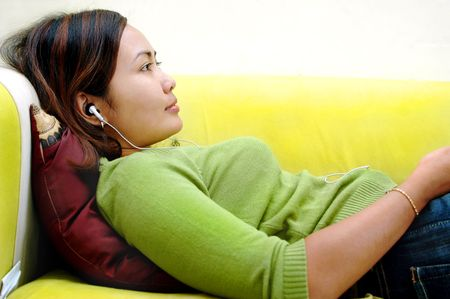 women relaxing on the sofa while listening to the music photo