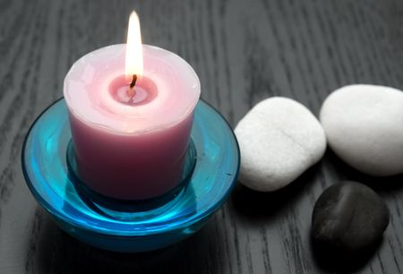 Candle with black and white stones - closeup photo