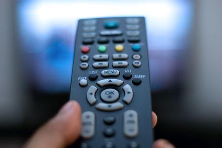 テレビとテレビのリモコンを持っているクローズ アップ手 写真素材