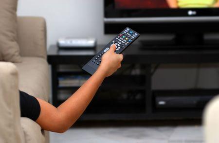 デジタル ライフ スタイル - 手、テレビのリモコンのボタンを押す