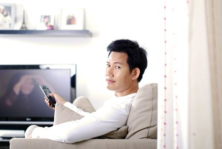 programme: Man changing TV channel using remote control