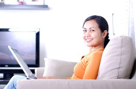 女性の similing 顔でコンピューターでの作業