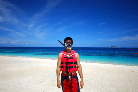 redang: Man with snorkeling equipment by the beach Stock Photo
