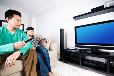 一緒にテレビを見るカップル 写真素材