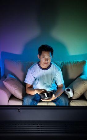watching movie: Man watching television alone at night Stock Photo