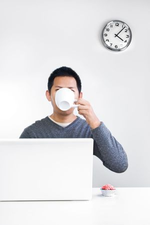 Man having a tea break at his desk Stock Photo