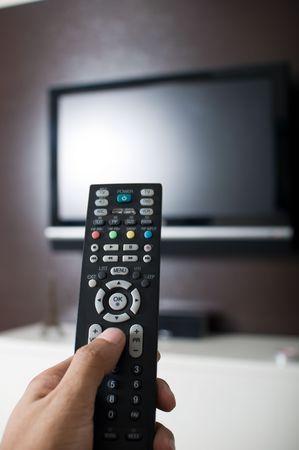 テレビのリモコンを持っている手 写真素材