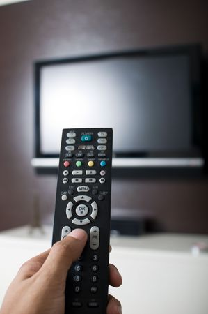 hand holding TV remote control Stock Photo