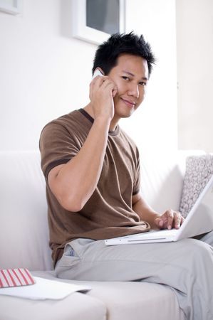 ネット サーフィンしながら携帯電話で話している男性インターネット