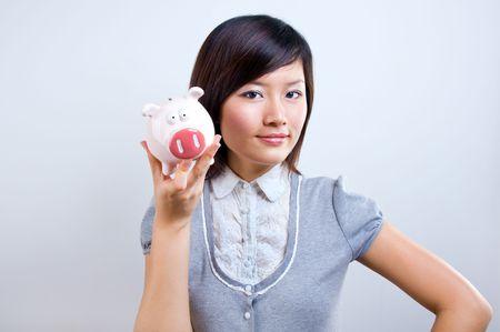 貯金箱を保持する女性