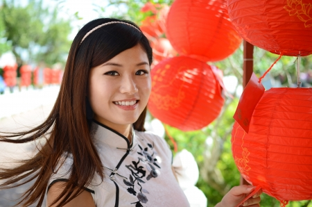 Picture of young chinese woman wearing traditional cheongsam with smiling face holding a red lantern Stock Photo