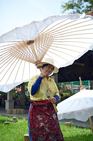 Chiang Mai, Thailand - May, 12 2012 : Woman holding big white wooden umbrella taken at umbrella factory