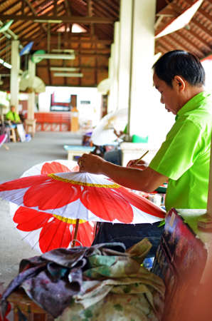 Chiang Mai, Thailand - May, 12 2012 : Man making a traditional wooden umbrella in umbrella factory Stock Photo - 13860807