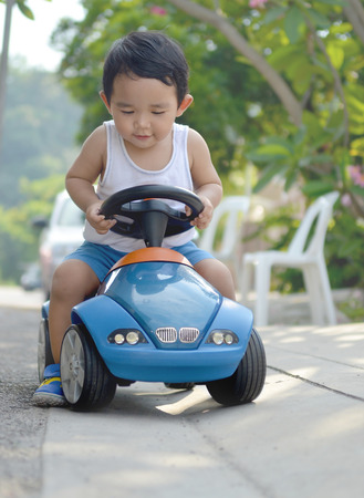 Asian baby boy rides his toy car