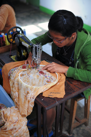 maker: Bukit Tinggi, Indonesia - July 27 2009: Close up of woman sewing a flora pattern on the fabric. Kain Sulam is local traditional cloth and Bukit Tinggi is one of the best \