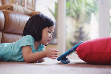 one little girl: Candid picture of baby girl watching video on tablet