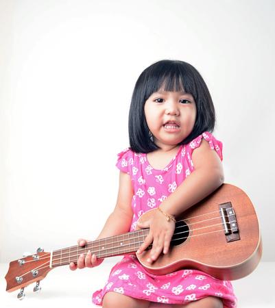 music education: Little girl playing ukulele Stock Photo