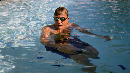 treading: Man treading water in swimming pool wearing goggles Stock Photo