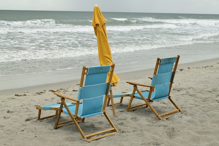 Pair of wooden beach chairs and umbrella on Cocoa Beach, Florida. Stock Photo