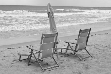 cocoa beach: Pair of wooden beach chairs and umbrella on Cocoa Beach, Florida. Stock Photo