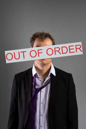 Stressed businessman with out of order sign in front of his head