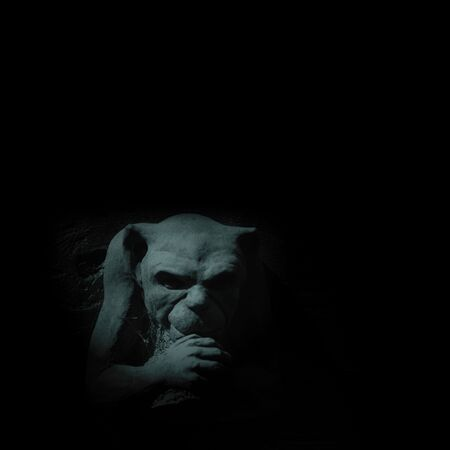 grotesque: Gargoyle figure on black Stock Photo