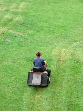 Man cutting grass with lawnmower photo