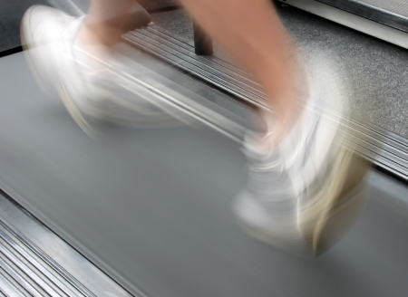 Man jogging on exercise treadmill in local gym. photo