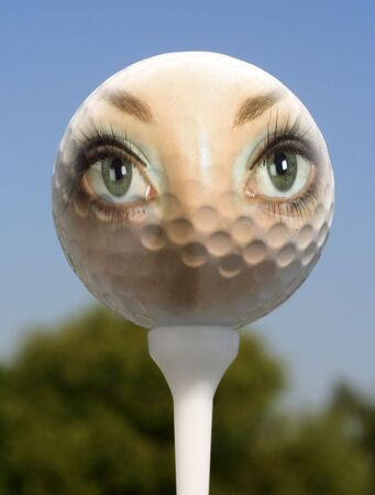 Womans face overlaid on to golf ball on tee. photo